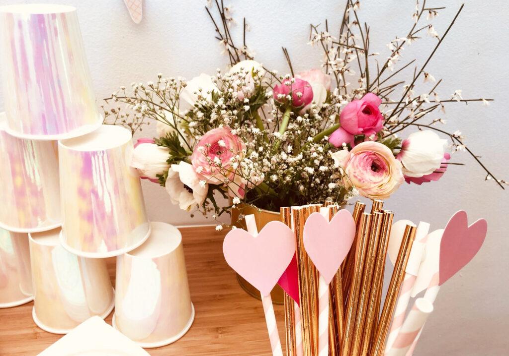 Zoom sur le coins gobelets irisés, fleurs de décoration et pailles cœurs.