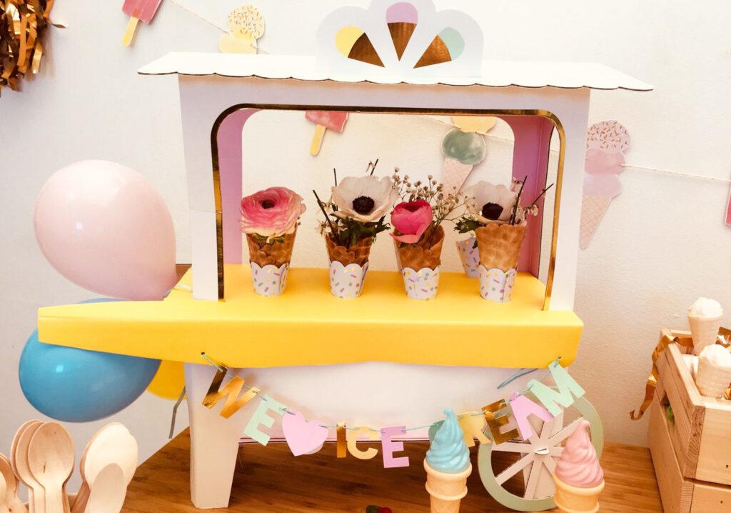 Reproduction d'un stand de vente de glaces décoré de ballons dans des tons pastels, d'objets déco en forme de glaces et d'une guirlande « We ice cream ».