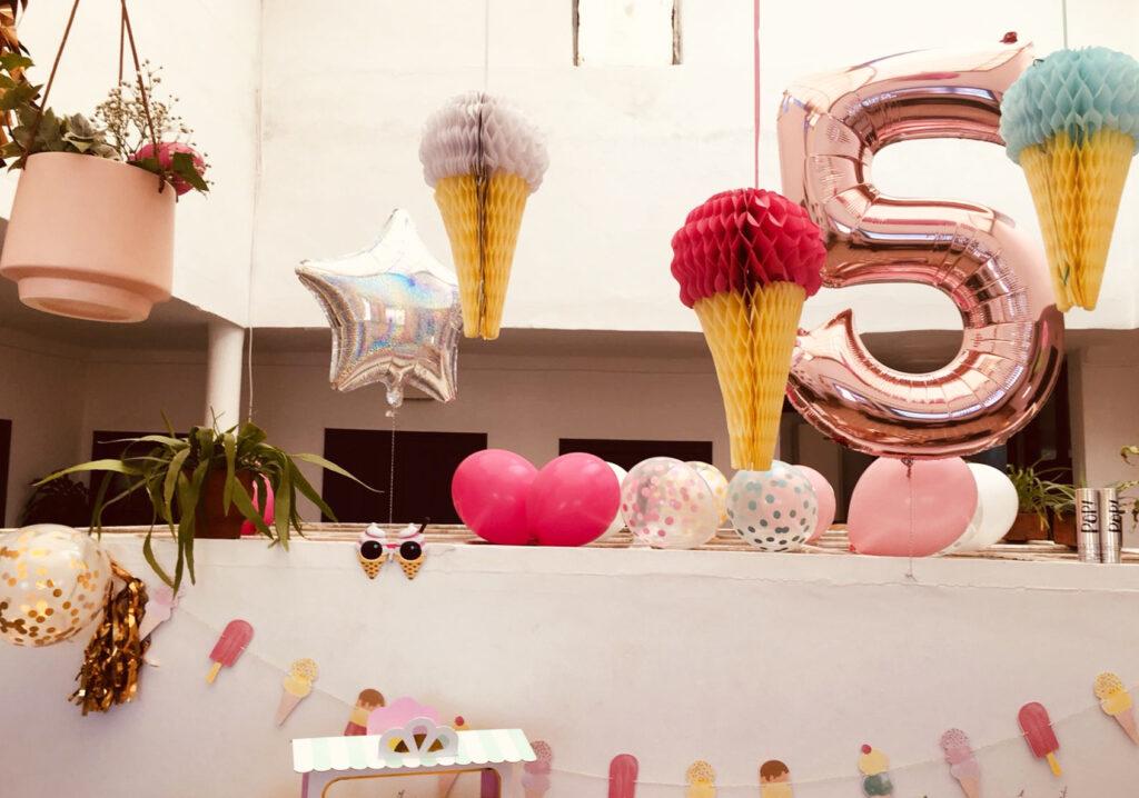 Les décorations suspendues et le grand ballon chiffre rose 5